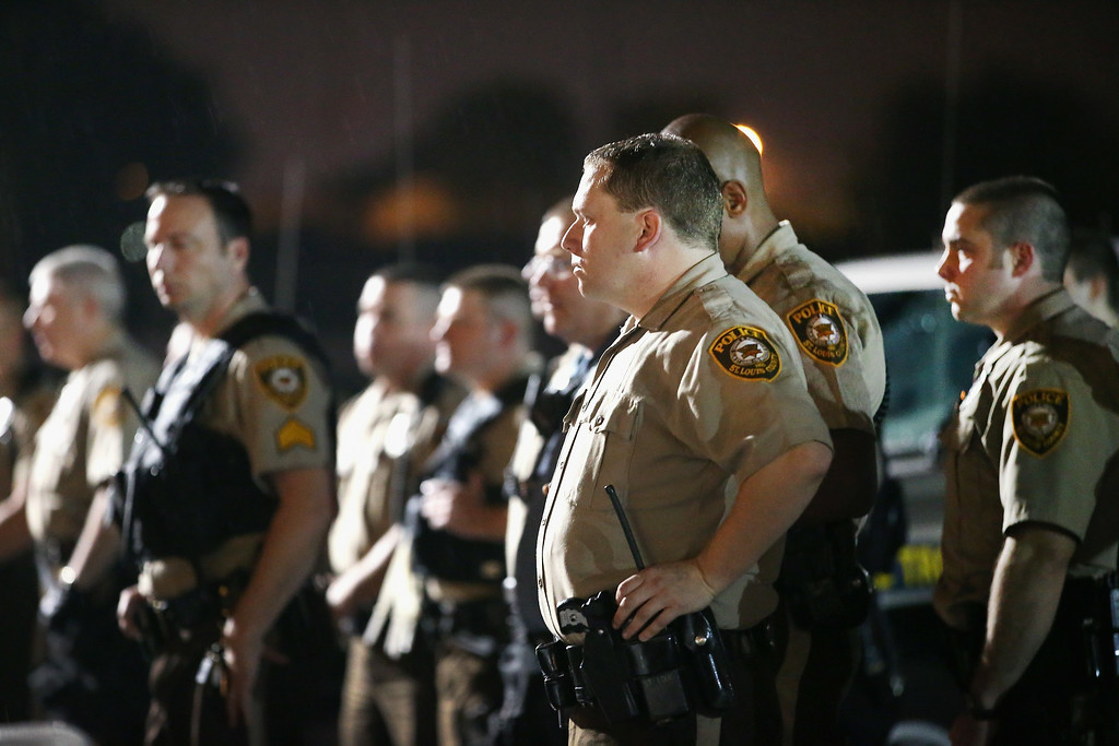 . FERGUSON, MO - AUGUST 15:  Missouri State Highway Patrol officers listen to taunts from demonstrators during a protest over the shooting of Michael Williams on August 15, 2014 in Ferguson, Missouri. As the taunts became more aggressive the troopers called in the county police then left. County police ended up shooting pepper spray,  smoke, gas and flash grenades at protestors before retreating. Several businesses were looted as the county police sat in formation with armored personnel carriers (APC) nearby. Violent outbreaks have taken place in Ferguson since the shooting death of Brown by a Ferguson police officer on August 9.  (Photo by Scott Olson/Getty Images)