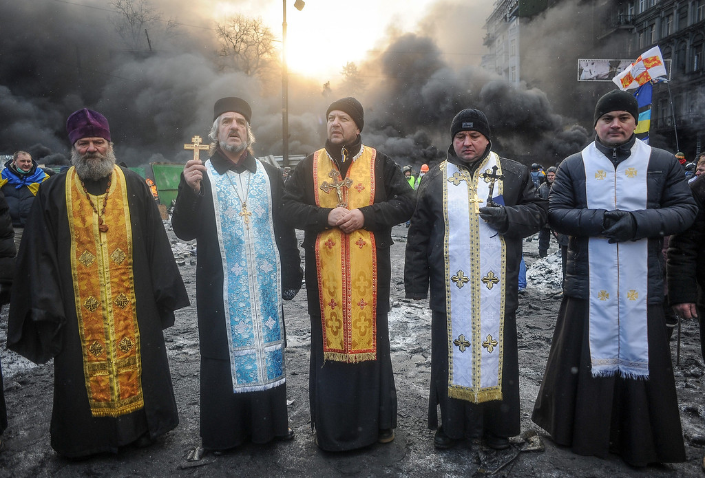 . Ukrainian priests stay in front of the burning barricade during an anti-government protest in downtown Kiev, Ukraine, 23 January 2014.  EPA/ROMAN PILIPEY