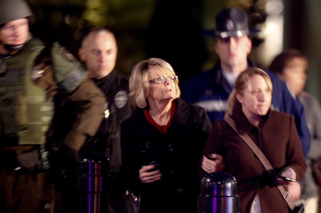 . People look on outside Clackamas Town Center in Clackamas, Ore., where a shooting occured Tuesday, Dec. 11, 2012. A gunman opened fire in the Portland, Ore., area shopping mall Tuesday, killing at least one person and wounding an unknown number of others, sheriff\'s deputies said. (AP Photo/The Oregonian, Bruce Ely)