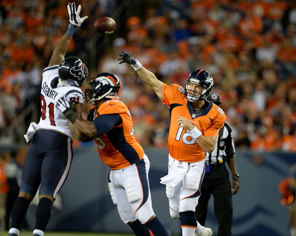 . DENVER, CO - AUGUST 23: Denver Broncos quarterback Peyton Manning (18) throws a pass over Houston Texans defensive end Lawrence Sidbury (91) during eh second quarter August 23, 2014 at Sports Authority Field at Mile High Stadium. (Photo by John Leyba/The Denver Post)