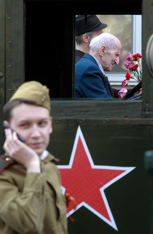 . World War II veterans ride a car as a member of a historical military club wearing Soviet army uniform speaks on a phone during the celebration of Victory Day in St.Petersburg, Russia, Thursday, May 9, 2013. Russia is celebrating the anniversary of victory over Germany in WWII. (AP Photo/Dmitry Lovetsky)