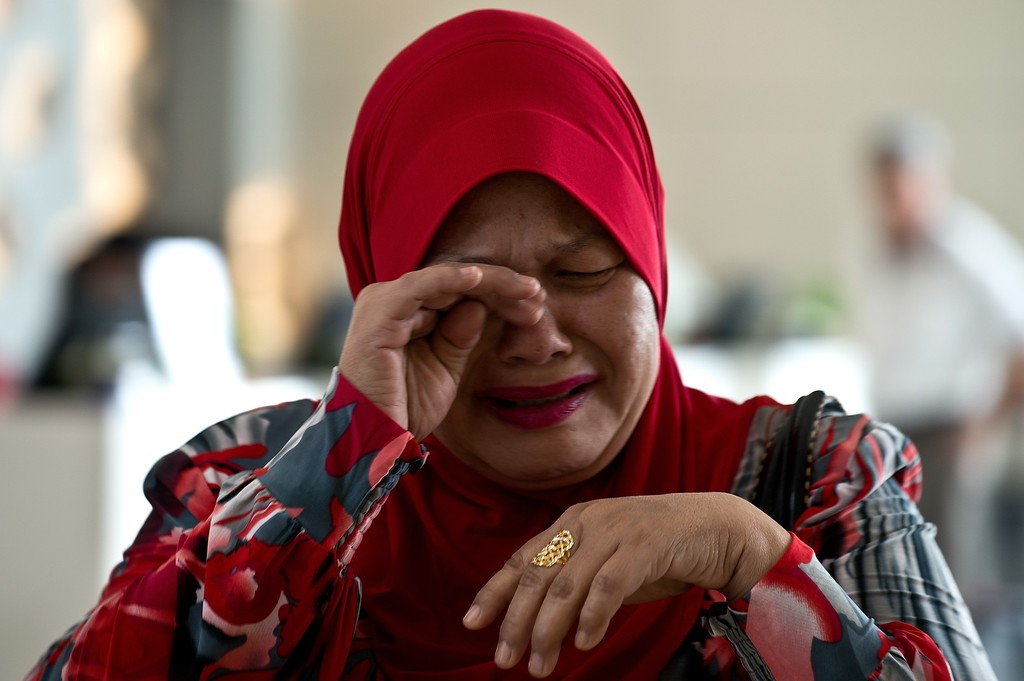 . A relative of a passenger on board missing Malaysia Airlines (MAS) flight MH370 cries as she arrives at the Everly hotel in Putrajaya on March 12, 2014. Malaysia\'s air force chief said authorities have not ruled out the possibility a missing airliner inexplicably changed course before losing contact, but denied reports the jet had been detected far from its planned flight path.    AFP PHOTO / MANAN VATSYAYANA/AFP/Getty Images