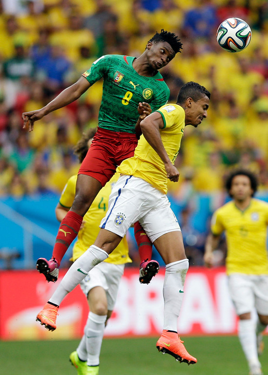 . Cameroon\'s Benjamin Moukandjo, left, and Brazil\'s Luiz Gustavo go for a header during the group A World Cup soccer match between Cameroon and Brazil at the Estadio Nacional in Brasilia, Brazil, Monday, June 23, 2014. (AP Photo/Andre Penner)