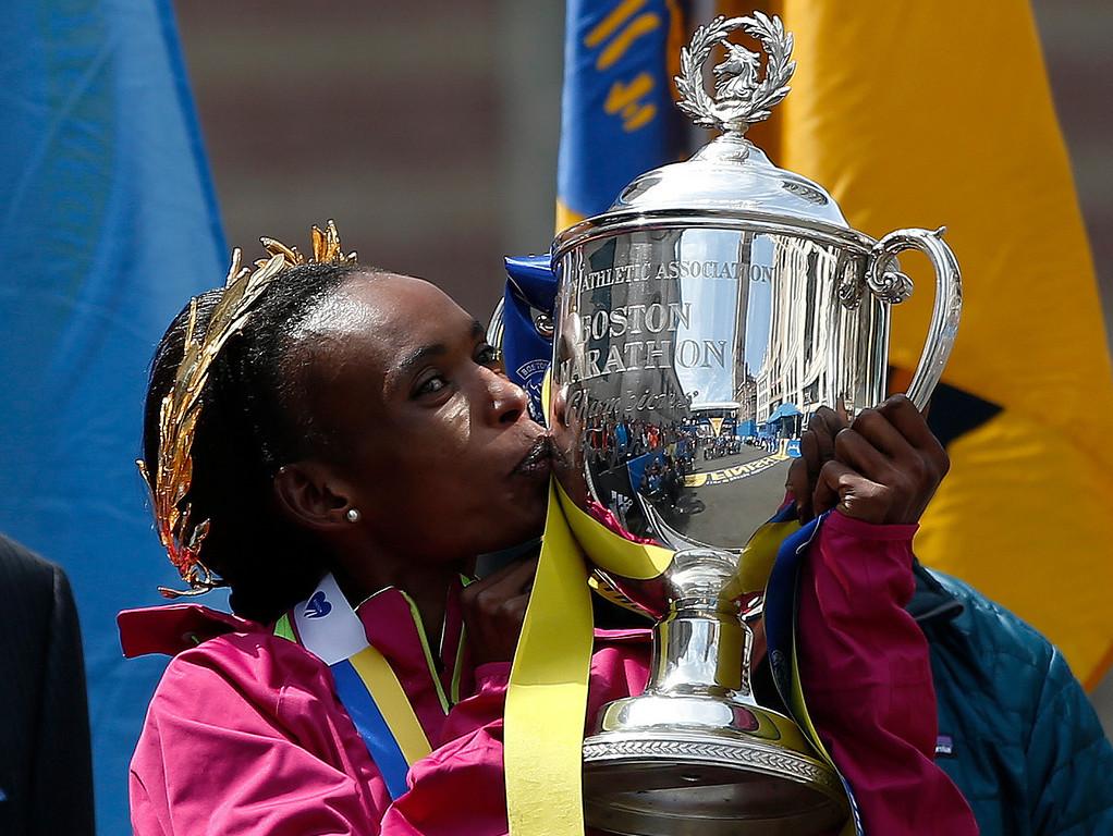 . Rita Jeptoo, of Kenya, kisses the trophy after winning the women\'s division of the 118th Boston Marathon Monday, April 21, 2014 in Boston. (AP Photo/Elise Amendola)