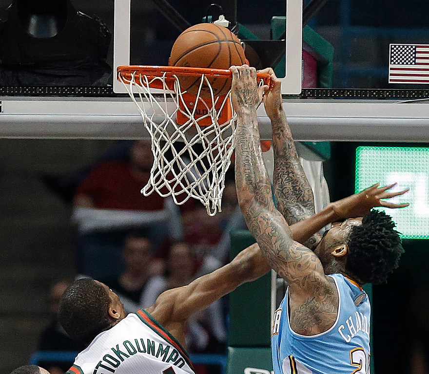 . Denver Nuggets\' Wilson Chandler, right, dunks on the Milwaukee Bucks\' Giannis Antetokounmpo during the second half of an NBA basketball game Thursday, Feb. 20, 2014, in Milwaukee. (AP Photo/Jeffrey Phelps)