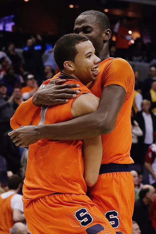 . Syracuse guard Michael Carter-Williams (1) is hugged by center Baye Keita (12) after an East Regional semifinal against Indiana in the NCAA men\'s college basketball tournament, Thursday, March 28, 2013 in Washington. Syracuse defeated Indiana 61-50. (AP Photo/Pablo Martinez Monsivais)