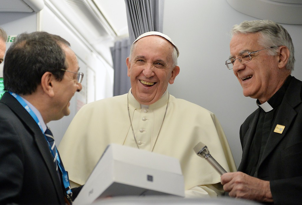 . Pope Francis (C) and father Federico Lombardi (R) greet a journalist of the papal flight upon arrival in Rio de Janeiro on July 22, 2013.    AFP PHOTO/LUCA ZENNARO/POOL