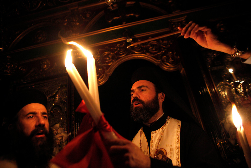 . A Greek Orthodox priest passes the Holy Fire to worshipers during an Easter Mass at the church of Agii Anargyri in Athens, late Saturday, April 19, 2014. The Holy Fire is brought in Greece every year from the church of the Holy Sepulcher in Jerusalem traditionally believed to be the burial site of Jesus Christ . (AP Photo/Kostas Tsironis)