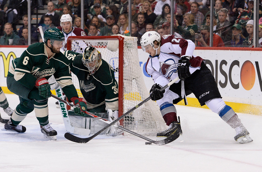 . Colorado Avalanche center Nathan MacKinnon (29) attempts a wrap around shot but gets the puck poked away by Minnesota Wild defenseman Marco Scandella (6) during the first period April 28, 2014 in Game 6 of the Stanley Cup Playoffs at Xcel Energy Center.  (Photo by John Leyba/The Denver Post)
