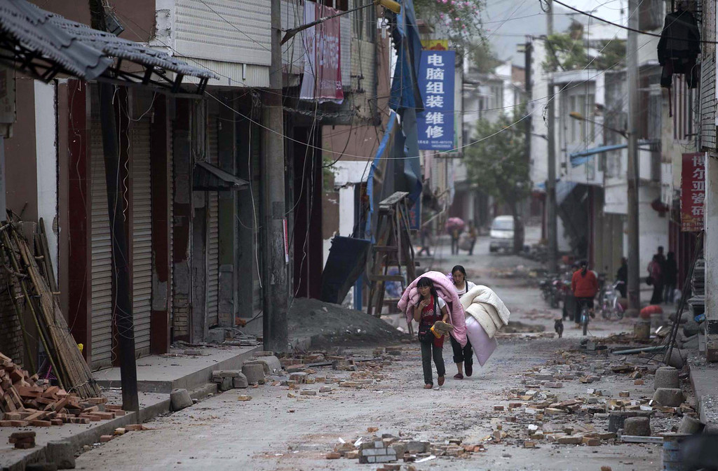 . In this photo released by China\'s Xinhua news agency, people carrying their belongings walk in quake-damaged Gucheng Village, Longmen Township, Lushan County, southwest China\'s Sichuan Province, Saturday, April 20, 2013. A powerful earthquake struck the steep hills of Sichuan province Saturday, nearly five years after a devastating quake wreaked widespread damage across the region. (AP Photo/Xinhua, Fei Maohua)