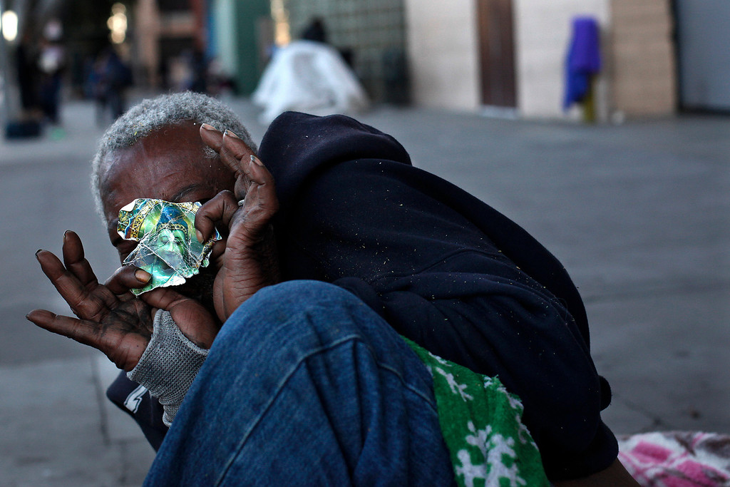 . A homeless man holds a torn piece of paper showing a painting of the Buddha in the Skid Row area of Los Angeles, Tuesday, March 12, 2013. (AP Photo/Jae C. Hong)