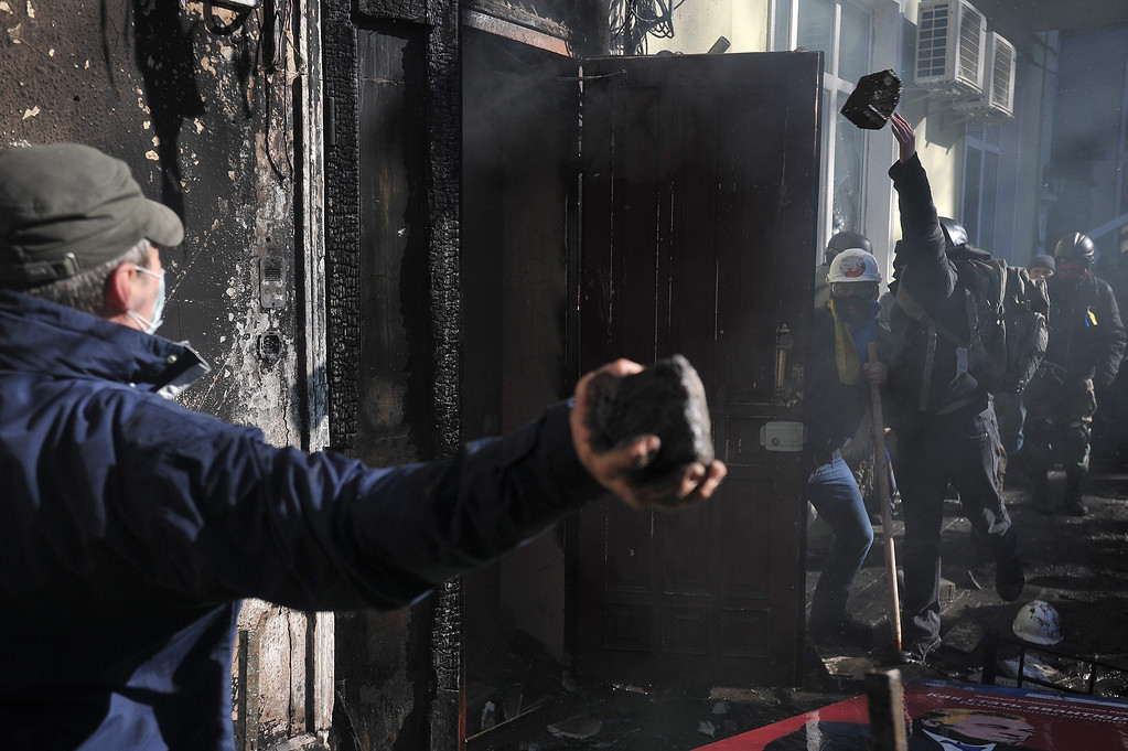 . Protesters throw stones as they try to enter the building with riot policemen inside during an anti-government protest in downtown Kiev, Ukraine, 18 February 2014. A least three protesters were killed in clashes with police on 18 February, Ukrainian opposition activists say.  EPA/ALEXEY FURMAN