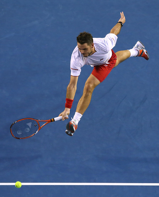 . Stanislas Wawrinka of Switzerland reaches out for a shot to Tomas Berdych of the Czech Republic during their semifinal at the Australian Open tennis championship in Melbourne, Australia, Thursday, Jan. 23, 2014.(AP Photo/Eugene Hoshiko)