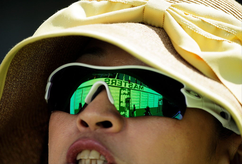 . Izumi Noami, from Japan, studies the leader board on the first fairway during the third round of the Masters golf tournament Saturday, April 12, 2014, in Augusta, Ga. (AP Photo/Charlie Riedel)