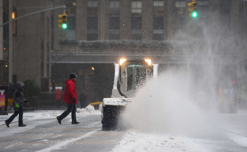 . A snow blower clears a path on a pedestrian walk way during a snow storm in New York, January 22, 2014. AFP PHOTO/Emmanuel DUNAND/AFP/Getty Images