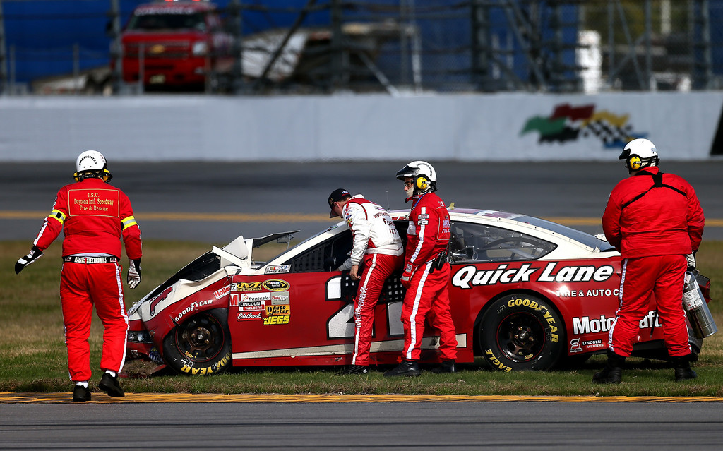 . Safty workers assist Trevor Bayne out of the #21 Motorcraft/Quick Lane Tire & Auto Center Ford after an incident in the NASCAR Sprint Cup Series Budweiser Duel 1 at Daytona International Speedway on February 21, 2013 in Daytona Beach, Florida.  (Photo by Jonathan Ferrey/Getty Images)