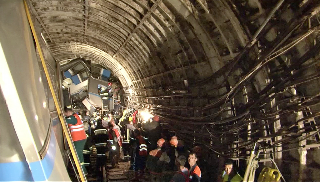 . In this frame grab provided by the Russian Ministry for Emergency Situations shows frame grab from a video showing rescue teams working inside the tunnel where several cars of the wrecked train look almost coiled, occupying the entire space of the tunnel of Moscow subway in Moscow, Russia, on Tuesday, July 15, 2014. Workers were seen trying to force open the mangled doors of the car where dead bodies are supposed to be. A rush-hour subway train derailed in Moscow Tuesday, killing about a dozen people and injuring at least 150, emergency officials said. Several cars left the track in the tunnel after a power surge triggered an alarm, which caused the train to stop abruptly. (AP Photo/Russian Emergency Situation Ministry)