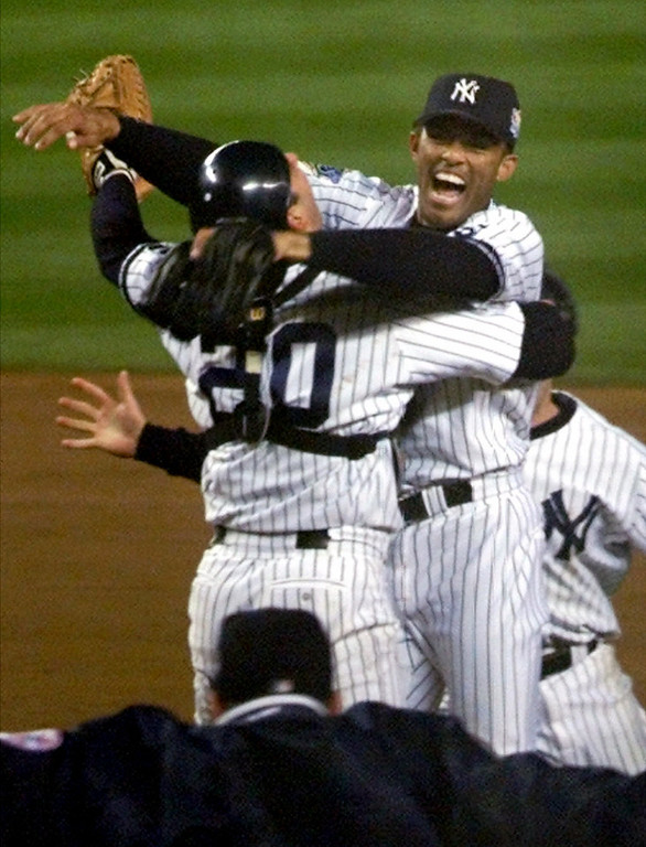 . New York Yankees pitcher Mariano Rivera jumps into the arms of catcher Jorge Posada after they defeated the Atlanta Braves 4-1 in game 4 of the World Series in New York, Wednesday, Oct. 27, 1999. The Yankees swept the series, 4-0. (AP Photo/Suzanne Plunkett)