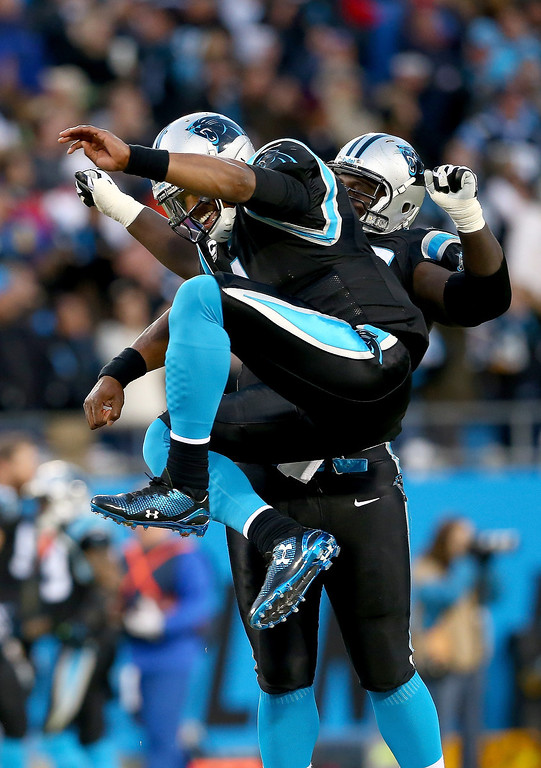 . Cam Newton #1 celebrates with teammate Byron Bell #77 of the Carolina Panthers after throwing a touchdown during their game against the New York Jets at Bank of America Stadium on December 15, 2013 in Charlotte, North Carolina.  (Photo by Streeter Lecka/Getty Images)