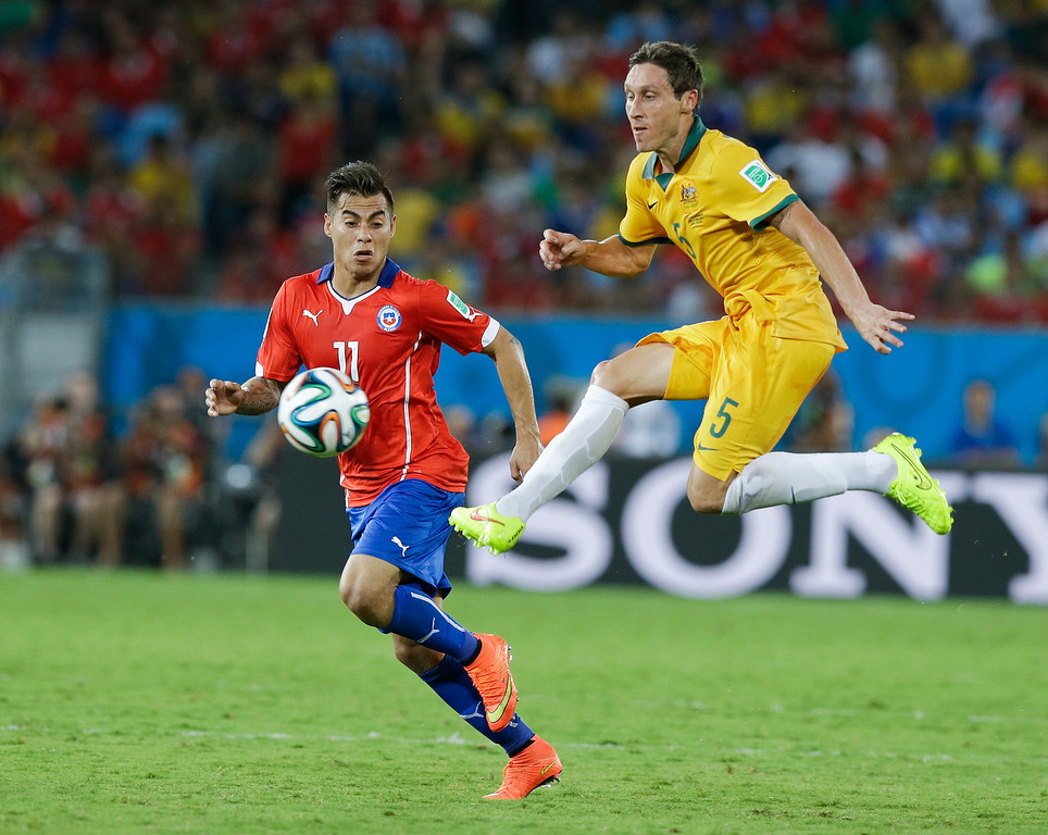 . Australia\'s Mark Milligan (5) kicks the ball past Chile\'s Eduardo Vargas (11) during the second half of the group B World Cup soccer match between Chile and Australia in the Arena Pantanal in Cuiaba, Brazil, Friday, June 13, 2014. (AP Photo/Thanassis Stavrakis)