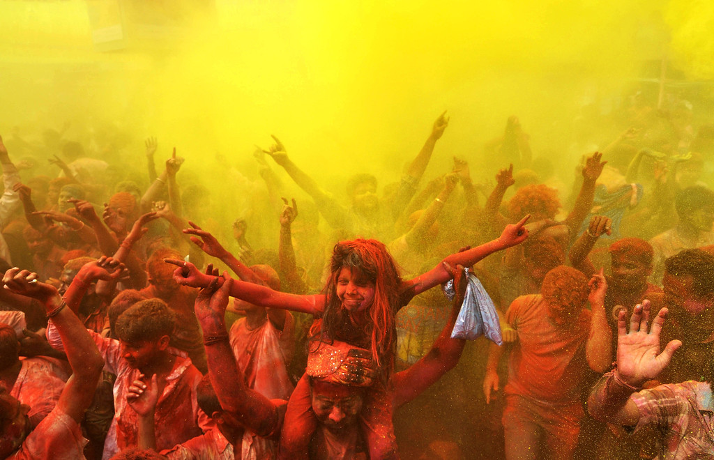 . Indian revelers cover each other with colored powder and dance while taking part in Holi festival celebrations in Guwahati on March 17, 2014. Holi, the Festival of Colors, is a popular Hindu spring festival observed in India and Nepal at the end of winter season on the last full moon day of the lunar month.  AFP PHOTO / Biju BOROBIJU BORO/AFP/Getty Images
