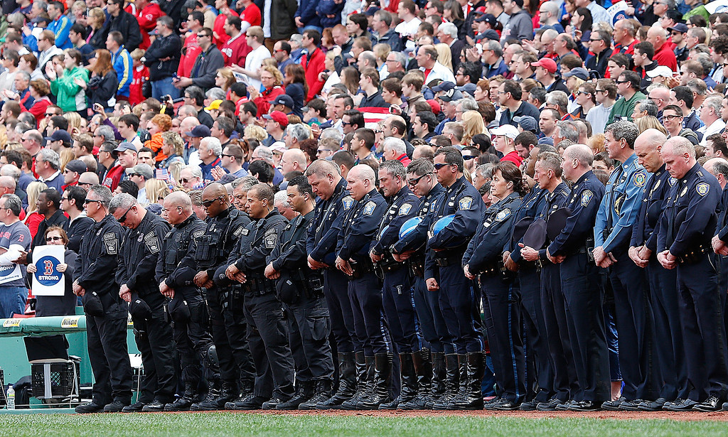 . BOSTON, MA - APRIL 20: Members of law enforcement react during pre-game ceremonies in honor of the Marathon bombing victims before a game between the Boston Red Sox and the Kansas City Royals at Fenway Park on April 20, 2013 in Boston, Massachusetts.  (Photo by Jim Rogash/Getty Images)