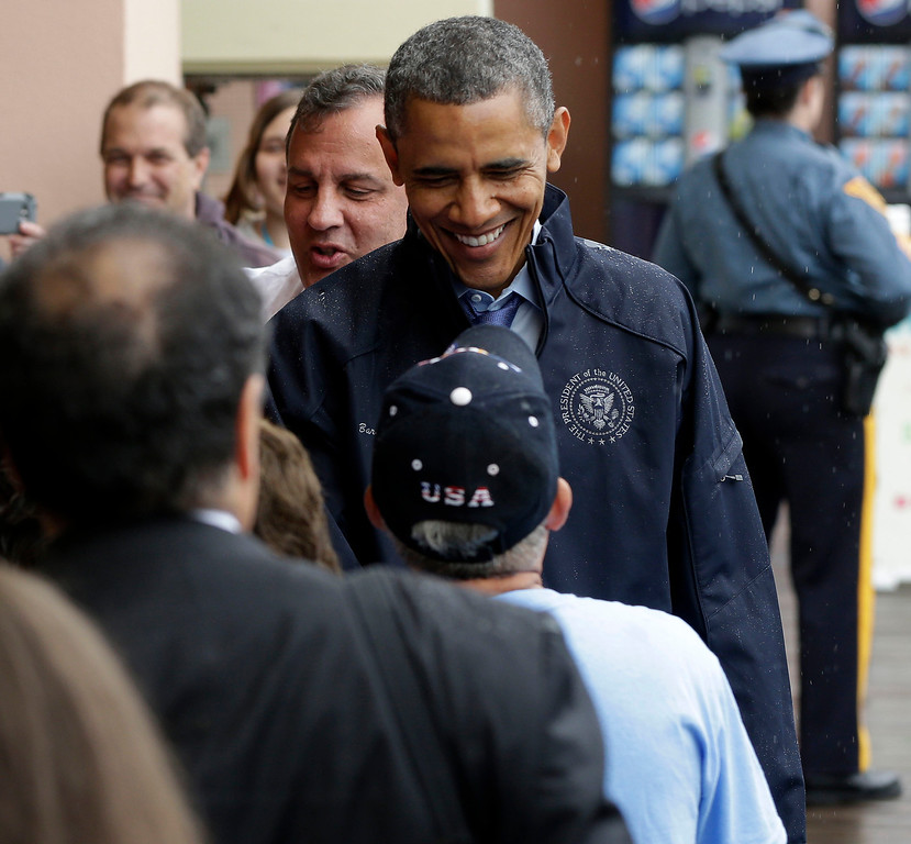. President Barack Obama, followed by New Jersey Gov. Chris Christie, greets guests during their visit to the boardwalk at Point Pleasant, NJ., Tuesday, May 28, 2013. (AP Photo/Pablo Martinez Monsivais)