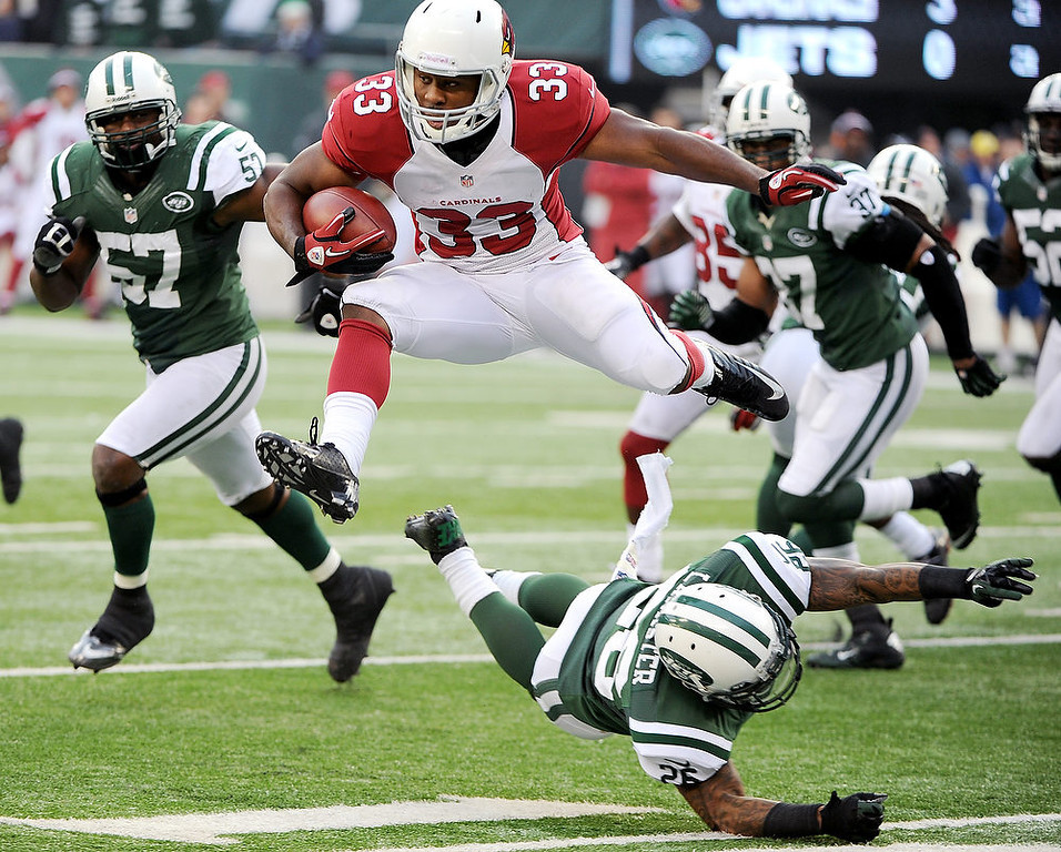 . Arizona Cardinals running back William Powell (33) leaps over New York Jets defensive back Ellis Lankster during the second half of an NFL football game, Sunday, Dec. 2, 2012, in East Rutherford, N.J. (AP Photo/Bill Kostroun)