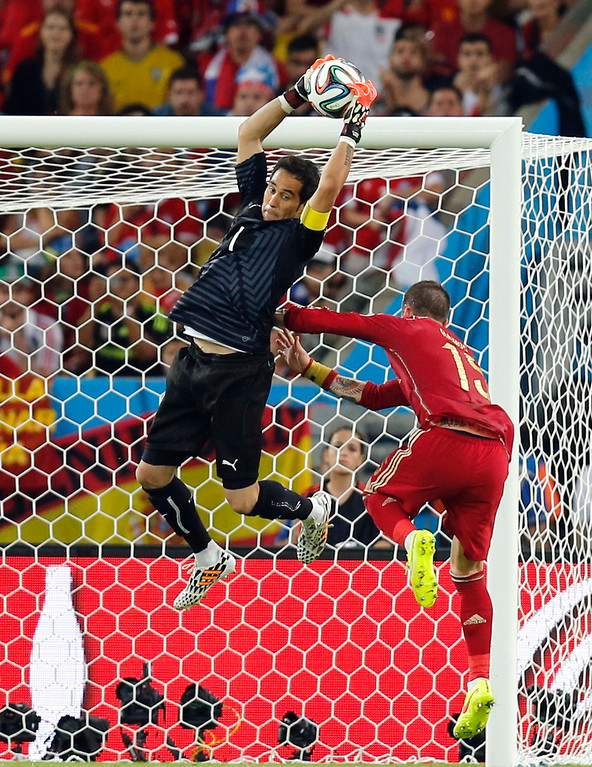 . Chile\'s goalkeeper Claudio Bravo makes a save against Spain\'s Sergio Ramos during the group B World Cup soccer match between Spain and Chile at the Maracana Stadium in Rio de Janeiro, Brazil, Wednesday, June 18, 2014.  (AP Photo/Frank Augstein)