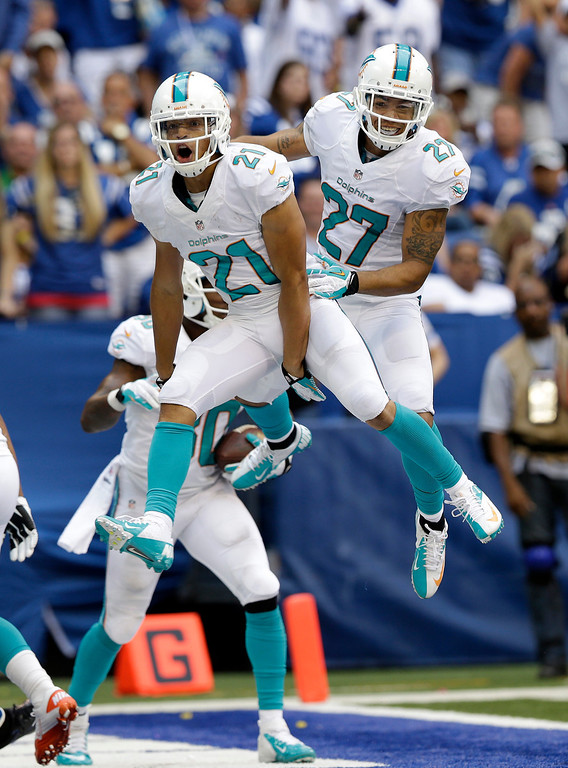 . Miami Diolphins\' Brent Grimes (21) celebrates with Jimmy Wilson (27) after Grimes intercepted a pass in the end zone intended for Indianapolis Colts\' Reggie Wayne during the second half an NFL football game Sunday, Sept. 15, 2013, in Indianapolis. (AP Photo/Michael Conroy)