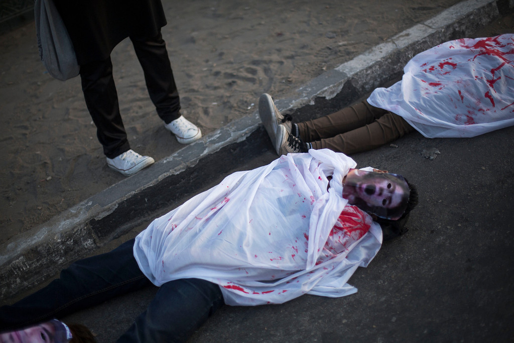 . Egyptian protesters dressed with fake blood on their shrouds while they perform during a protest against the release of former Egypt\'s dictator Hosni Mubarak in Cairo, Egypt, Thursday, Aug. 22, 2013. (AP Photo/Manu Brabo)