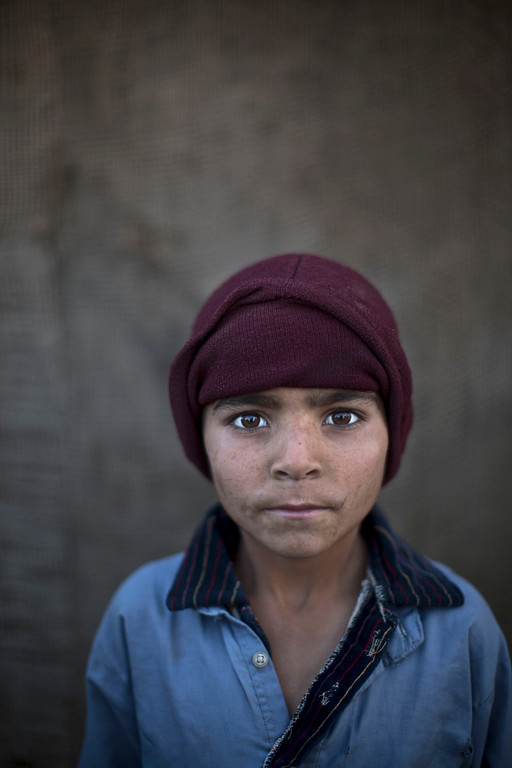 . In this Sunday, Jan. 26, 2014 photo, Afghan refugee boy, Noorkhan Zahir, 6, poses for a picture, while playing with other children in a slum on the outskirts of Islamabad, Pakistan. For more than three decades, Pakistan has been home to one of the world�s largest refugee communities: hundreds of thousands of Afghans who have fled the repeated wars and fighting their country has undergone. Since the 2002 U.S.-led invasion of Afghanistan, some 3.8 million Afghans have returned to their home country, according to the U.N.�s refugee agency. (AP Photo/Muhammed Muheisen)