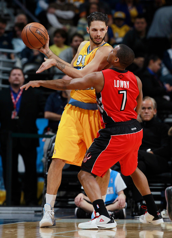 . Denver Nuggets guard Evan Fournier, left, looks to pass the ball as Toronto Raptors guard Kyle Lowry covers in the first quarter of an NBA basketball game in Denver, Friday, Jan. 31, 2014. (AP Photo/David Zalubowski)