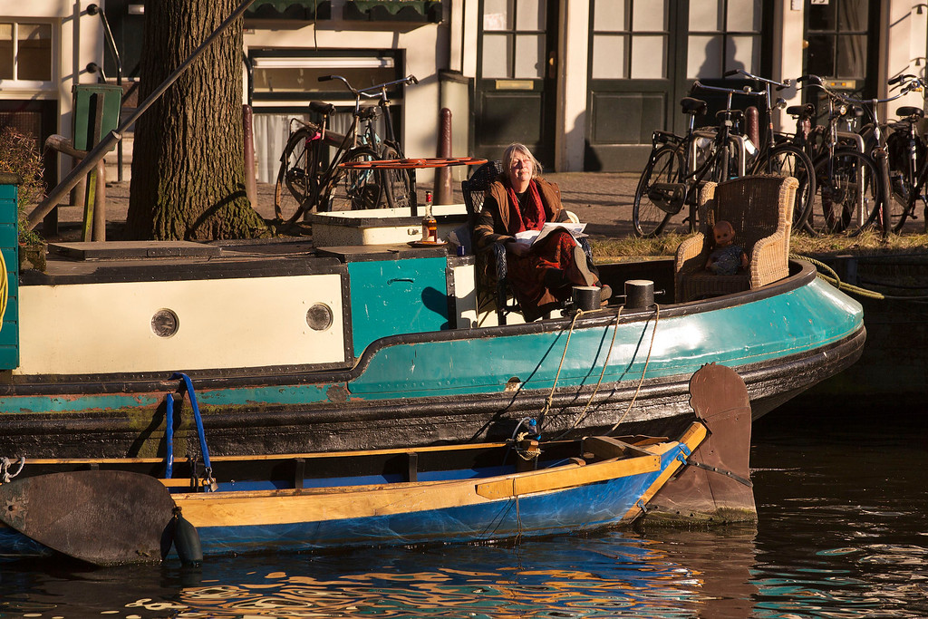 . A woman enjoys the afternoon sun while sitting on her houseboat at the Herengracht canal in Amsterdam April 2, 2013, 2013. The Royal celebrations in the Netherlands this week put the country and the capital Amsterdam on front pages and television screens around the world with an orange splash. There\'s plenty to see and do in 48 hours in this compact city, where the world-famous Rijksmuseum only recently reopened after an extensive renovation. Picture taken April 2, 2013. REUTERS/Michael Kooren