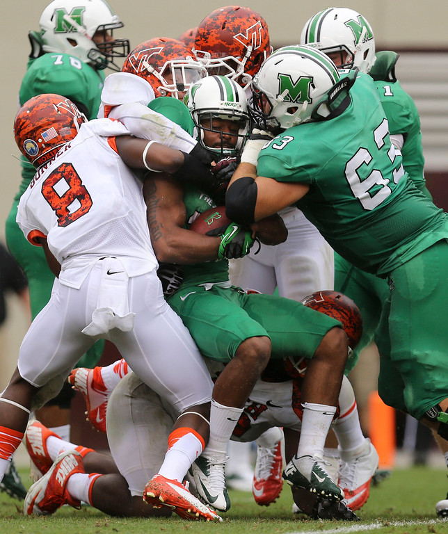 . Marshall\'s Rakeem Cato, center, is swallowed up by Virginia Tech defenders during the first half of an NCAA college football game Saturday, Sept. 21 2013,  in Blacksburg Va. (AP Photo/The Roanoke Times, )