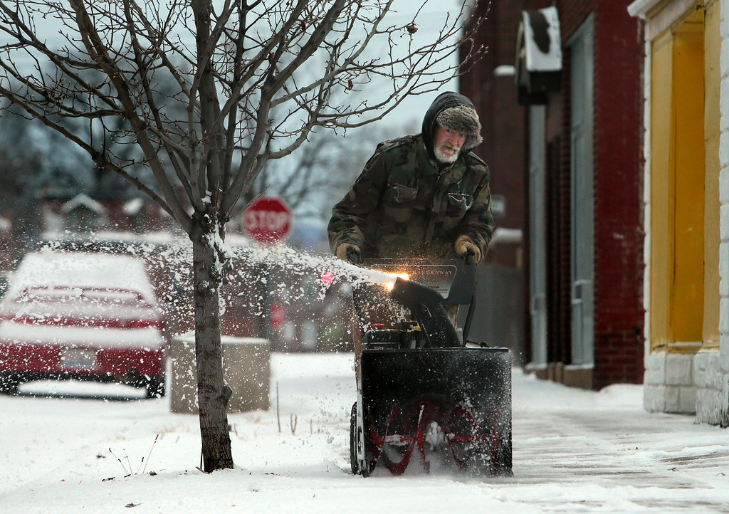 . Handyman Warren Page cleans the sidewalk outside Lamb\'s Bride Child Care Center  Thursday, Jan. 2, 2014, in St. Louis. Snow began falling Wednesday and continued into Thursday morning, coating the ground with 2- to 5-inches. (AP Photo/St. Louis Post-Dispatch, Laurie Skrivan)