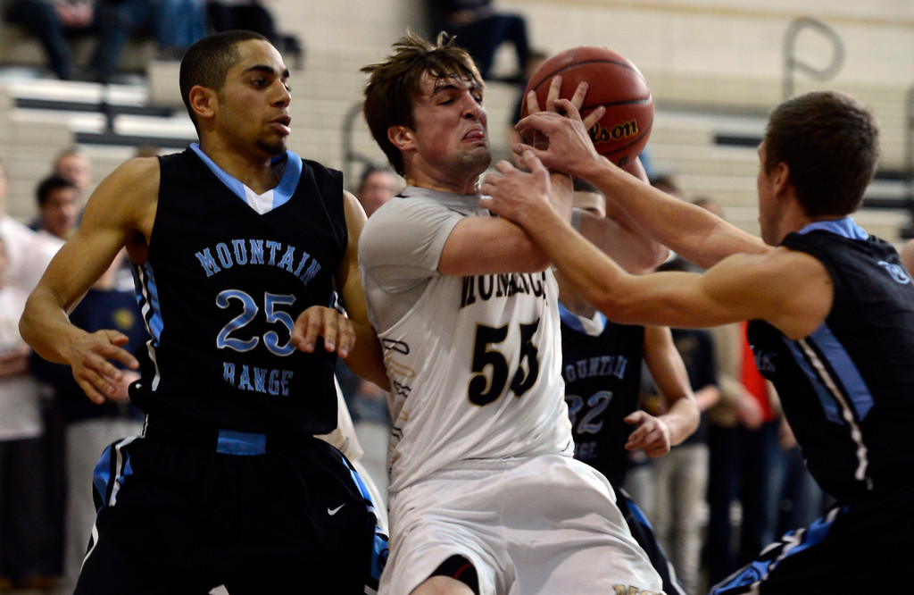 . LOUISVILLE, CO - JANUARY 3: Monarch\'s Jay MacIntyre (55) fights for control against Mountain Range\'s Elijah Cone (25) and Tyler Sullivan (4). Monarch High School boys basketball takes on Mountain Range High School at Monarch High School in Louisville. (Photo by Kathryn Scott Osler/The Denver Post)
