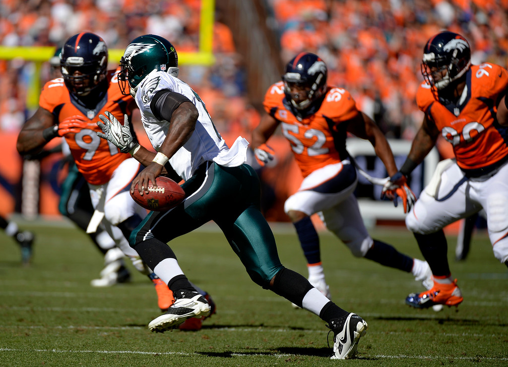 . Philadelphia Eagles quarterback Michael Vick (7) runs with the Denver Broncos defense after him during the first quarter.  (Photo by Joe Amon/The Denver Post)