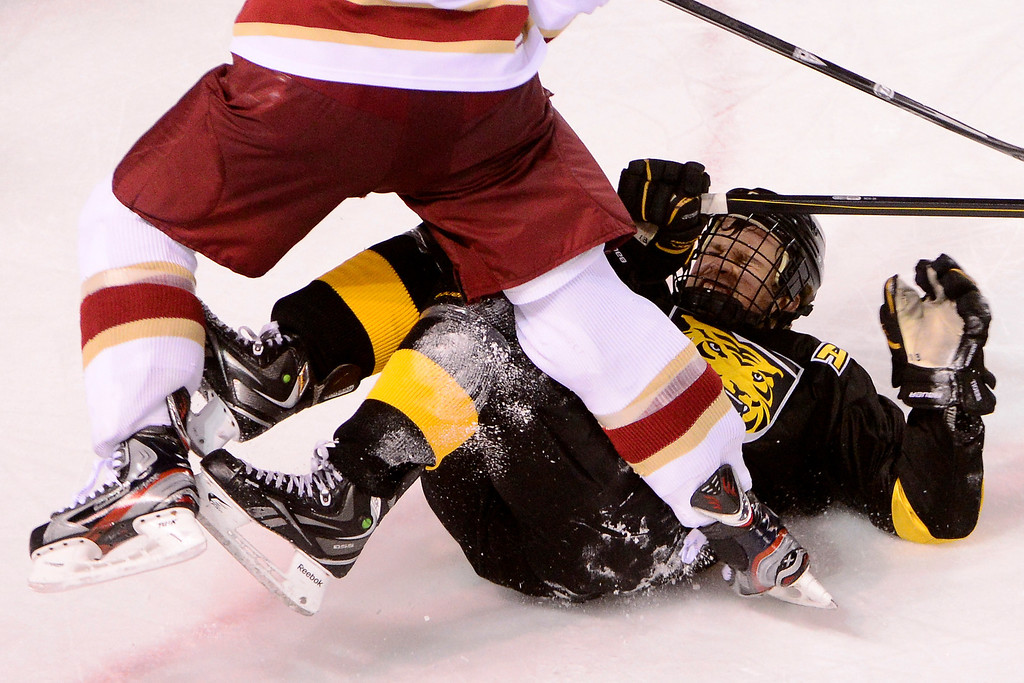 . DENVER, CO - MARCH 17: Rylan Schwartz (13) of the Colorado College Tigers hits the ice after taking a hit from David Makowski (10) of the University of Denver Pioneers during the third period of action. The University of Denver loses 4-3 to Colorado College during the WCHA playoffs at Magness Arena. (Photo by AAron Ontiveroz/The Denver Post)