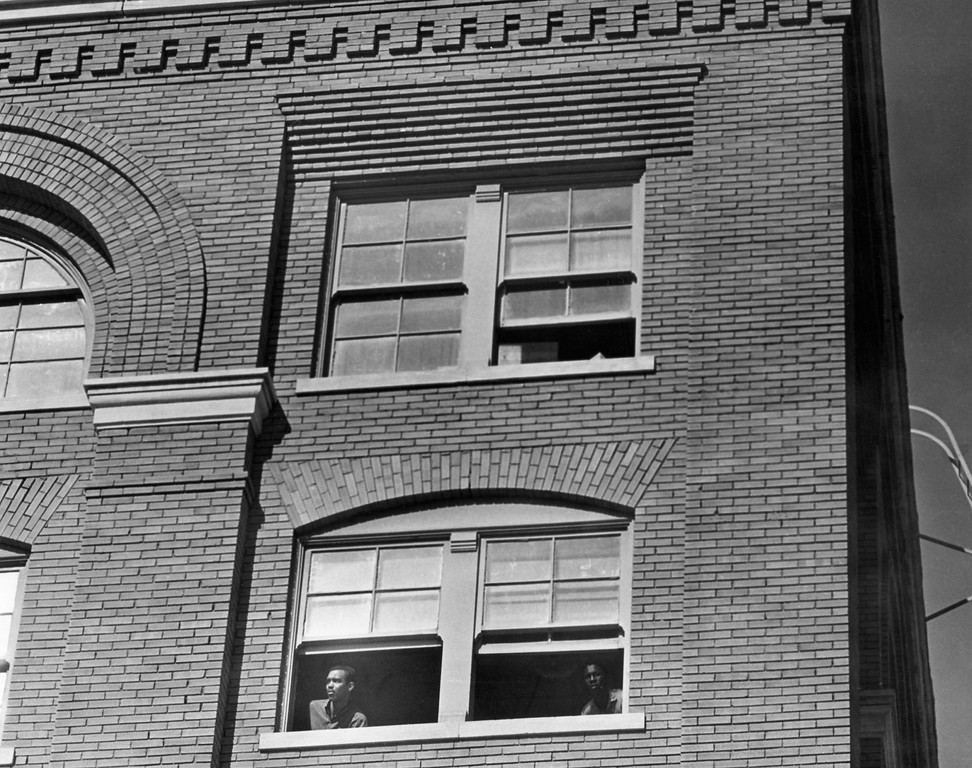 . Men peer out the fifth floor window of the Depository building shortly after the assassination. It was the floor above where an eyewitness reported seeing a man with a gun at the window before shots were fired. Tom Dillard/Dallas Morning News