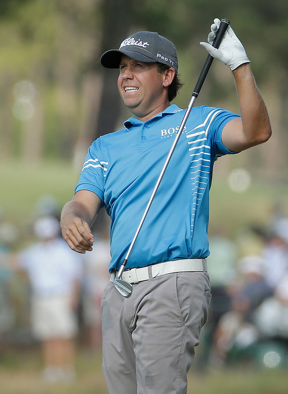 . Erik Compton reacts to his second shot on the 13th hole during the third round of the U.S. Open golf tournament in Pinehurst, N.C., Saturday, June 14, 2014. (AP Photo/Charlie Riedel)
