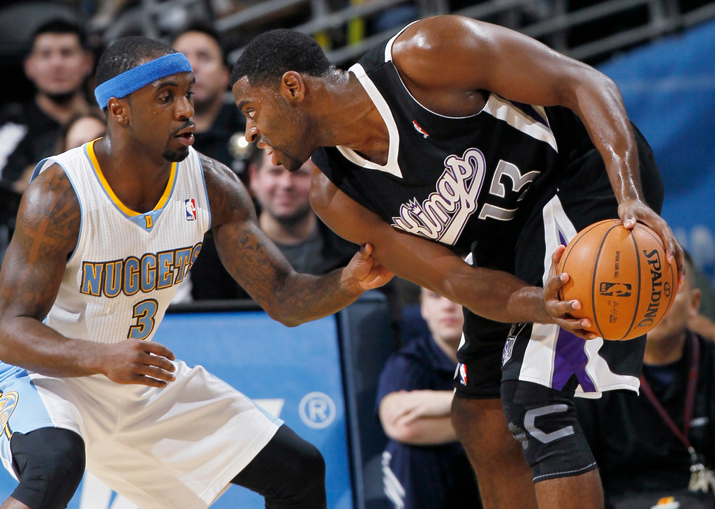 . Sacramento Kings guard Tyreke Evans, right, protects the ball from Denver Nuggets guard Ty Lawson during the third quarter of the Nuggets\' 121-93 victory in an NBA basketball game in Denver on Saturday, Jan. 26, 2013. (AP Photo/David Zalubowski)