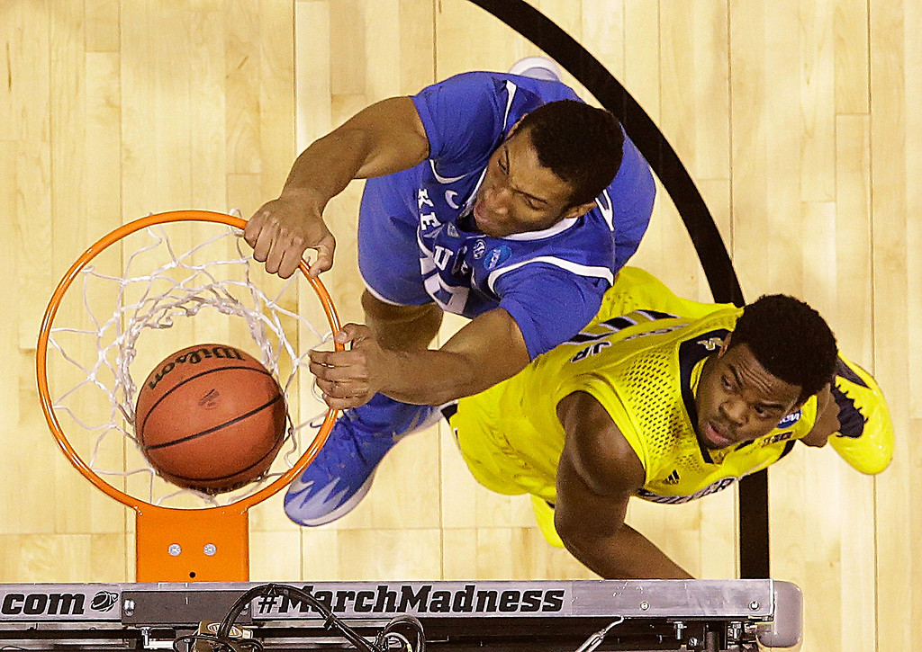 . Kentucky\'s Marcus Lee dunks in front of Michigan\'s Derrick Walton Jr. during the first half of an NCAA Midwest Regional final college basketball tournament game Sunday, March 30, 2014, in Indianapolis. (AP Photo/David J. Phillip)