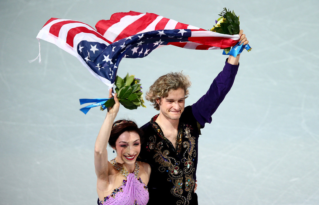 . Gold medalists Meryl Davis and Charlie White of the United States celebrate during the flower ceremony for the Figure Skating Ice Dance on Day 10 of the Sochi 2014 Winter Olympics at Iceberg Skating Palace on February 17, 2014 in Sochi, Russia.  (Photo by Clive Mason/Getty Images)