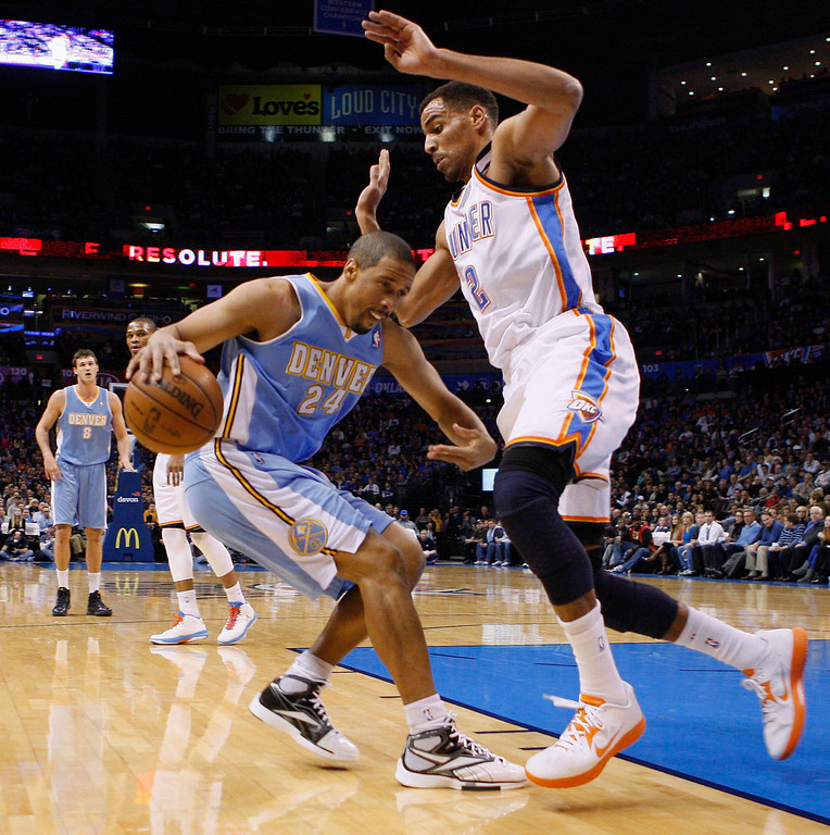 . Denver Nuggets guard Andre Miller (L) is topped by the defense of Oklahoma City Thunder guard Thabo Sefolosha (R) in the first half of their NBA basketball game in Oklahoma City, Oklahoma January 16, 2013. REUTERS/Bill Waugh