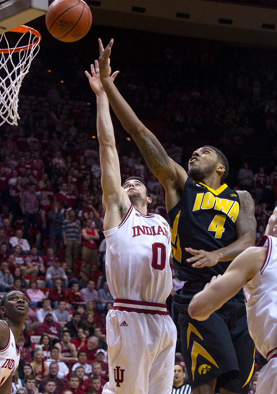 . Iowa\'s Roy Devyn Marble (4) slips past Indiana\'s Will Sheehey (0) to shoot in the first half of an NCAA college basketball game on Thursday, Feb. 27, 2014, in Bloomington, Ind. (AP Photo/Doug McSchooler)