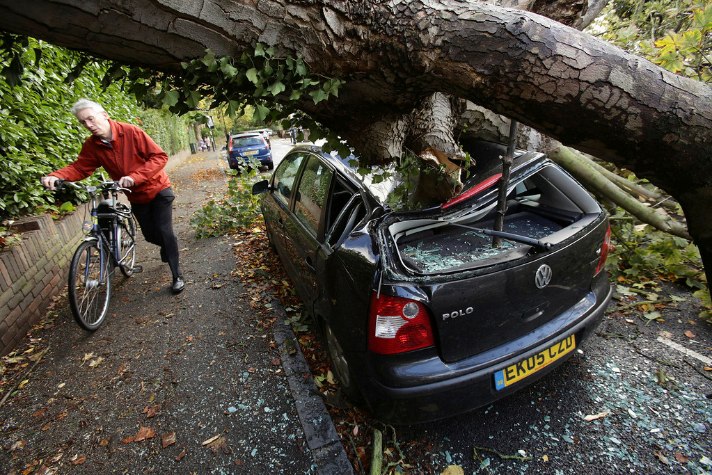 . A car is crushed under a fallen tree as a man pushes a bicycle nearby following a storm, in Hornsey, north London, Monday Oct. 28, 2013. (AP Photo/PA, Yui Mok)