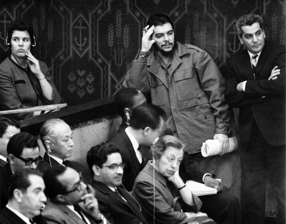 """. Cuba\'s Ernesto \""""Che\"""" Guevara, smoking a cigar and in uniform, leans against a wall in the spectator\'s gallery in the United Nations Security Council chamber, Dec. 14, 1964, as he listens to speech by U.S. ambassador to the U.N. Adlai Stevenson. Cuba has no seat in the Security Council. Guevara had to stand as there were no more chairs for spectators. (AP Photo/Harry Harris)"""