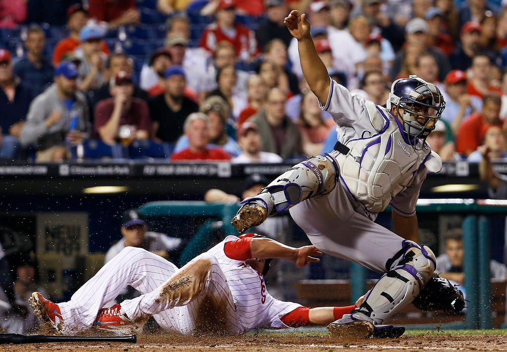 . Philadelphia Phillies\' Carlos Ruiz, left, collides with Colorado Rockies catcher Wilin Rosario after being forced out at home on ball hi by Ben Revere during the third inning of a baseball game, Tuesday, May 27, 2014, in Philadelphia. (AP Photo/Matt Slocum)