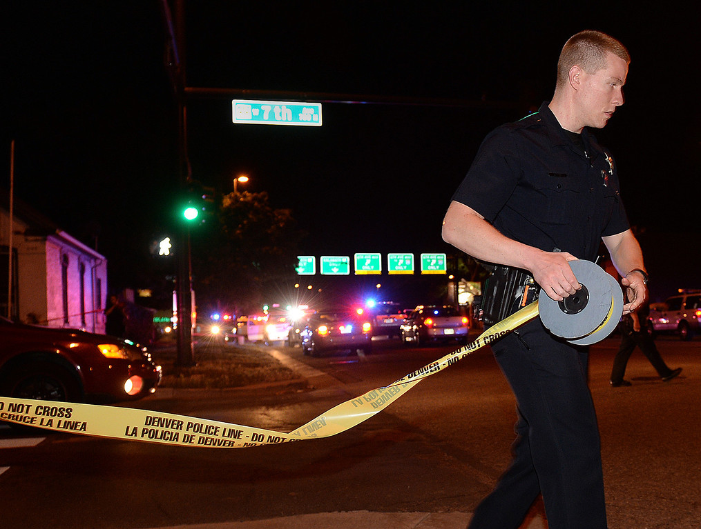 . A Denver Police officer put up crime scene tape to block off the intersection at 7th and Kalamath Thursday night. Denver Police investigated a shooting that occurred at Red Rocks AmphitheaterThursday night, June 19, 2014. Photo by Karl Gehring/The Denver Post